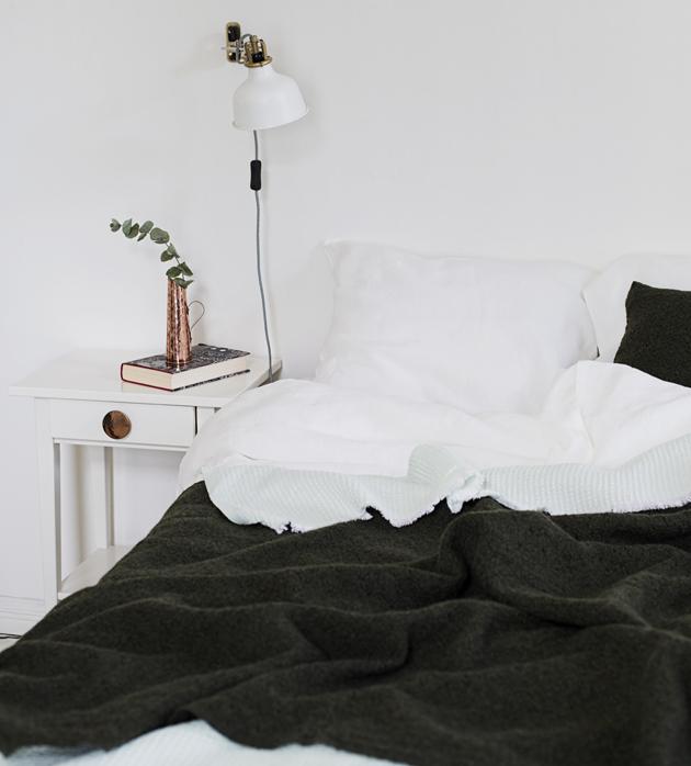 Minimalisti petaa makuuhuoneen sängyn vähillä vuodevaatteilla.