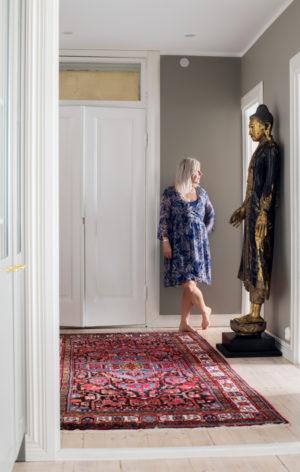 Vappu Pimiä uuden kotinsa eteisessä. Koti on täynnä upeaa taidetta.